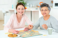 Elderly woman playing board game Stock Images