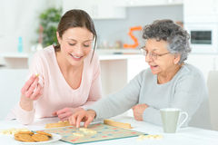 Elderly woman playing board game Stock Photography