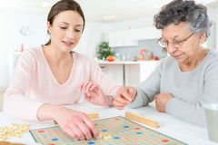 Elderly woman playing board game Royalty Free Stock Images
