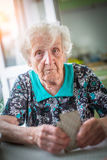 An elderly woman playing cards. royalty free stock photos