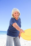 Elderly woman playing freesby. Closeup of elderly woman playing freesby royalty free stock image