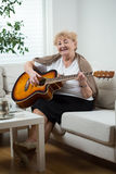Elderly woman playing the guitar Royalty Free Stock Photography