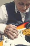 Elderly woman playing guitar. Royalty Free Stock Image