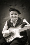 Elderly woman playing guitar. Royalty Free Stock Image