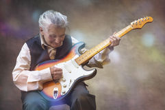 Elderly woman playing guitar. Royalty Free Stock Images