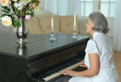 Elderly woman playing the piano at home Royalty Free Stock Images