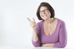 Elderly woman points a finger to the right. Royalty Free Stock Image