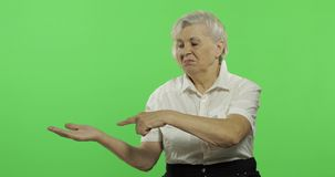 An elderly woman points at something and smiles. Old grandmother. Chroma key. An elderly woman points at something and smiles. Old pretty grandmother in a white stock video