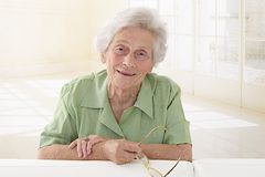 An elderly woman portrait holding glasses in her living room Royalty Free Stock Photos