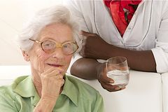 An elderly woman portrait holding glasses in her living room Stock Photos