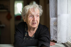 Elderly woman portrait at the kitchen table. Help. Royalty Free Stock Image
