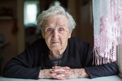 Elderly woman portrait, sitting in the house. Pensioner. Stock Photo
