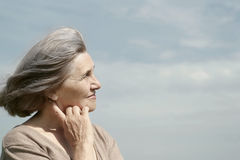 Elderly woman posing against the sky Stock Image