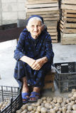 Elderly woman and potatoes Stock Photography