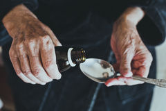 Elderly woman pours medicine in spoon to take medication, health care of elderly people concept Stock Photography