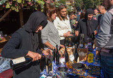 Elderly woman pours red wine made in the convent, during festival of Georgia Stock Photo