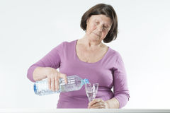 Elderly woman pours water into a glass. Royalty Free Stock Photography