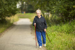 An elderly woman practices Nordic walking outdoors. Sport. Royalty Free Stock Photos