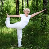 An elderly woman practices yoga Stock Image