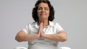 Elderly woman practicing yoga stock video footage