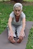 Elderly woman practicing yoga. Outdoors stock image