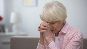 Elderly woman praying to God, asking for mercy and help, Christian tradition. Stock footage stock video footage