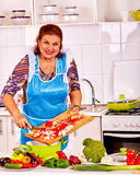 Elderly woman prepares food in the kitchen. Royalty Free Stock Photography
