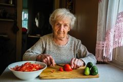 Elderly woman prepares a meal in a village house. Cooking. stock photo
