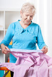 Elderly woman preparing shirt to ironing Royalty Free Stock Image