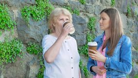 Elderly woman and pretty girl in a cotton jacket drinking coffee against the background of a wall of wild stone. stock video footage