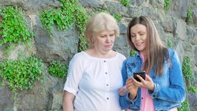 Elderly woman and pretty young girl using smartphone. Vintage wall of wild stone in the background. stock footage