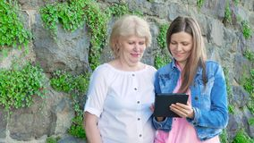Elderly woman and pretty young girl using tablet computer. Vintage wall of wild stone in the background. Elderly woman and pretty young girl using tablet stock footage