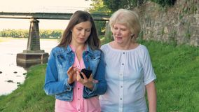 Elderly woman and pretty young girl walks along the waterfront using smartphone. stock video