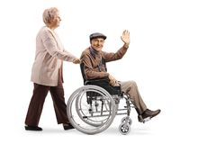 Elderly woman pushing an elderly man waving and sitting in a wheelchair royalty free stock image