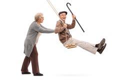 Elderly woman pushing a man on swing. Elderly women pushing a men on a wooden swing isolated on white background Stock Photo