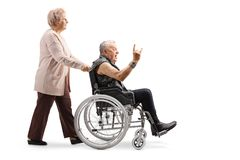Elderly woman pushing a mature man making a rock and roll hand sign in a wheelchair royalty free stock photo