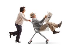 Elderly woman pushing a shopping cart with a mature man riding i Stock Photo