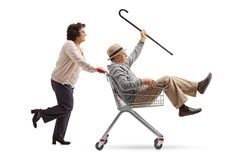 Elderly woman pushing a shopping cart with a senior riding inside stock images