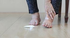 Elderly woman putting cream on swollen feet. At home royalty free stock images