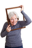 Elderly woman putting head through Royalty Free Stock Photography