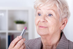 Elderly woman putting on lipstick Stock Images