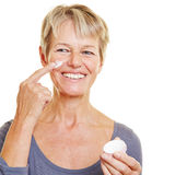 Elderly woman putting skin care Stock Image