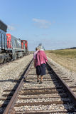 Elderly woman on the railroad track. Elderly woman walking down a railroad track Stock Photo
