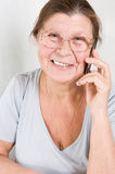 Elderly woman razgovariet on a mobile phone. Studio photography at the table on a light background Stock Photo