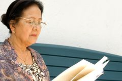 Elderly Woman Read A Book Outdoor Royalty Free Stock Photo