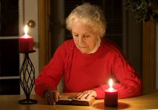 Elderly woman reading. Elderly lady sitting in candlelight reading the bible during a power outage stock photo