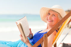 Elderly woman reading a book royalty free stock photo