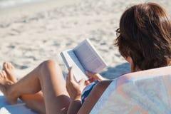 Elderly woman reading book on beach Royalty Free Stock Photos