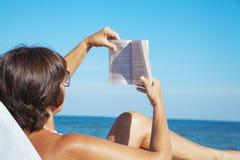Elderly woman reading book on beach stock photo