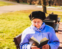 Elderly woman reading a book without glasses Royalty Free Stock Images